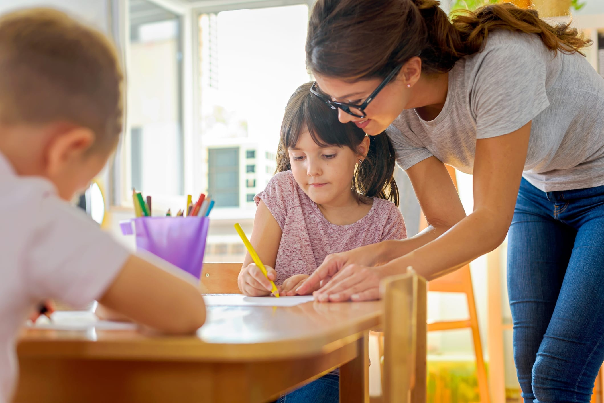 Children drawing with smiling preschool teacher assisting them